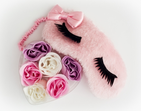 Pink sleeping mask and little heart made of fabric flowers on a white background.  Stock Photo