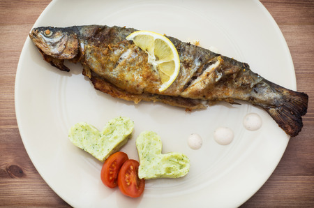 Delicious grilled fish with two hearts of mashed potatoes and cherry tomatoes. photo