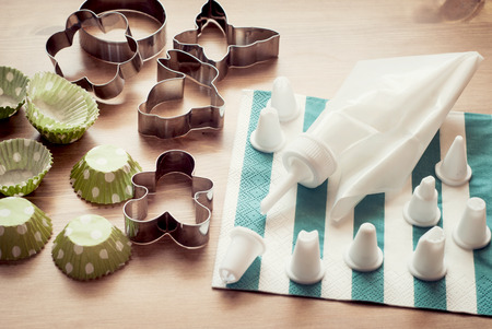 Piping bag set with cookie cutters and cups for cupcakes. Retro style. photo