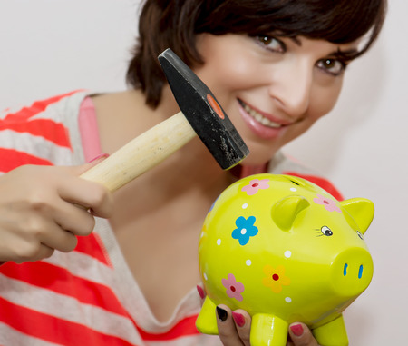 Young smiling woman breaks a porcelain piggy bank with a hammer. photo