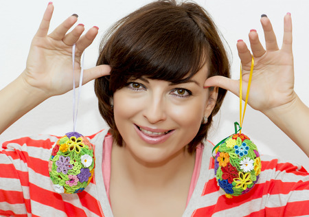 joking: Young caucasian woman joking with decorative easter eggs.