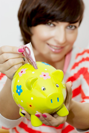 Young caucasian woman gives money to decorative ceramic piggy bank. photo