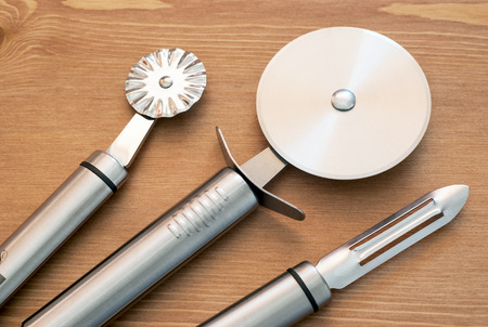 stainless steel kitchen: Set of new stainless steel kitchen tools on wooden background.