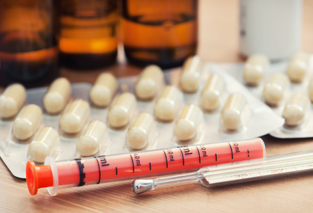 morbidity: Pharmacy pills, syringe and thermometer on the table.