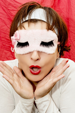 sleep mask: Attractive caucasian woman in sleep mask with a surprised look.