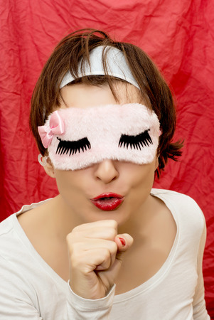 Young caucasian woman in sleeping mask imitates singing into a microphone. photo