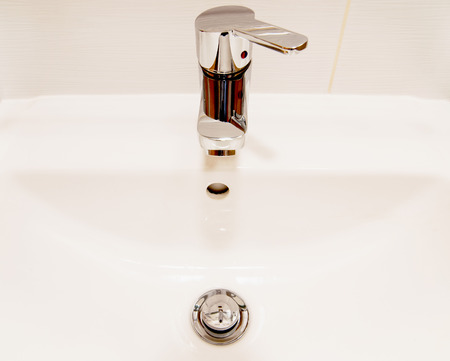 Pure white sink and chrome faucet with handle. photo