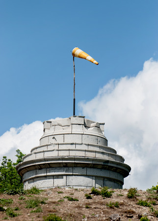 Windsock on the stone tower shows wind direction. photo