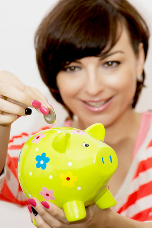 caucasian woman: Young caucasian woman gives a euro coin into decorative ceramic piggy bank.
