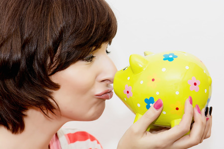 Young funny woman in profile and decorative ceramic piggy bank. photo
