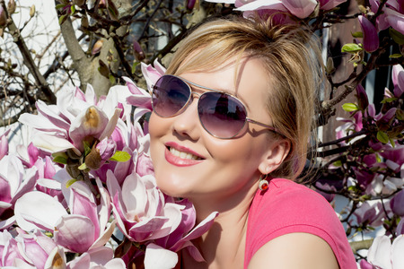 caucasian woman: Blonde caucasian woman and blooming magnolia. Spring theme.