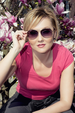 womens fashion: Blonde woman posing with blooming magnolia. Spring womens fashion. Stock Photo