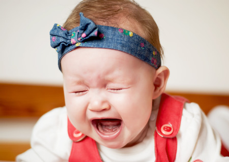 Little caucasian baby girl heart wrenching crying. photo