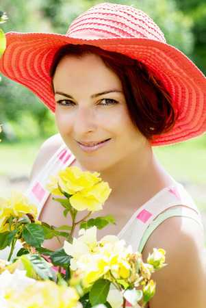 Beautiful caucasian woman in a red hat posing in the garden. photo