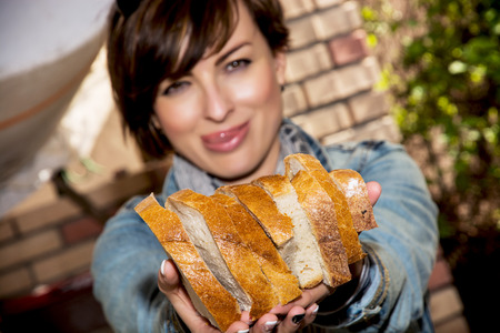 Young caucasian woman offering fresh sliced ​​bread.