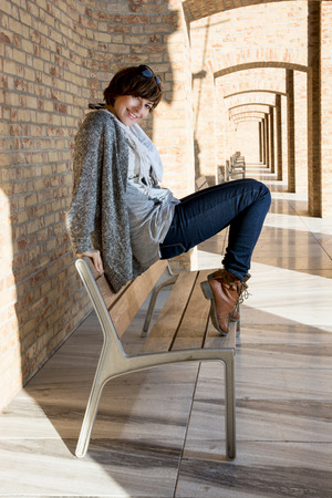 Beautiful caucasian brunette posing on a bench. photo