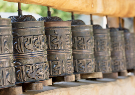 A prayer wheel is a cylindrical wheel on a spindle made from metal, wood, stone, leather or coarse cotton. Traditionally, the mantra Om Mani Padme Hum is written in Sanskrit on the outside of the wheel. photo