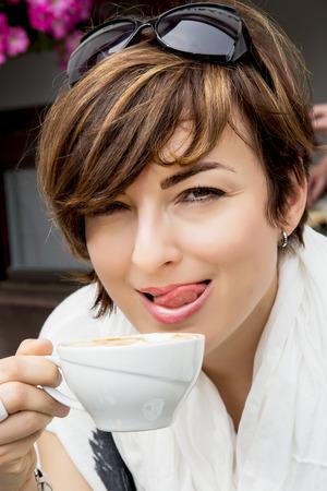 relishing: Beautiful young brunette relishing coffee. Stock Photo