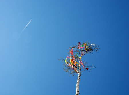 Looking up at may pole and aircraft on blue sky. European traditions.