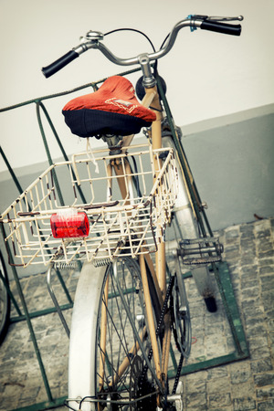 Old retro bicycle with empty metal basket.