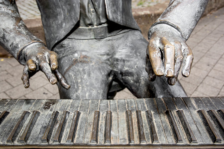 Pianist statue - detail of his fingers and piano keys. photo