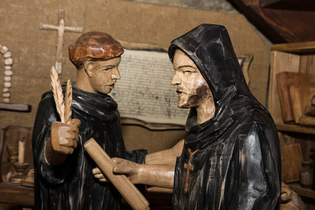 rewriting: Wooden statues - monks in the monastery. Rewriting of Holy Scripture in the old slavonic language.