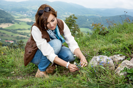 Young caucasian woman admires the flowers at the mountain meadow. photo