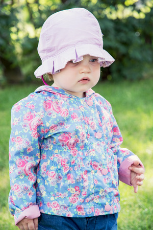 caucasian girl: Little caucasian girl in the modern jacket with hat. Childrens fashion.