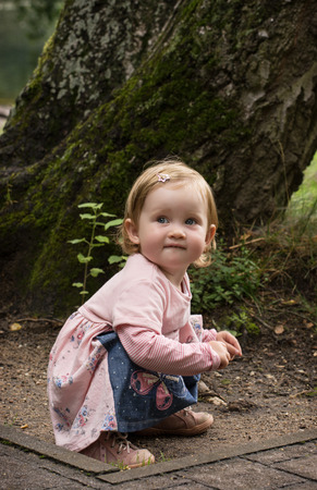 blond girl: Little caucasian blond girl in beautiful dress kneeling on the ground.