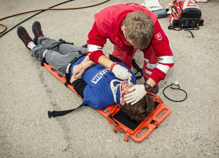 Nitra, Slovakia - September 06, 2014: Simulation of the car accident. Emergency service worker makes the control of vital functions.