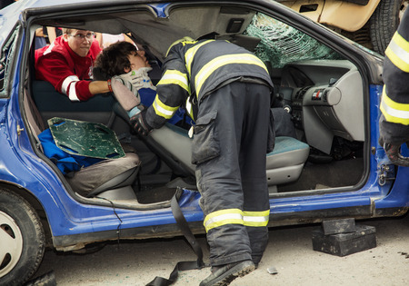 salvaging: Nitra, Slovakia - September 06, 2014: Simulation of the car accident. Rescue units saving the injured woman. Editorial