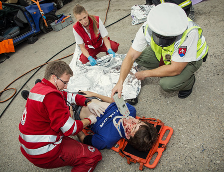 Nitra, Slovakia - September 06, 2014: Simulation of the car accident. Paramedics stabilizing the patient. Policeman makes the breath test for alcohol.