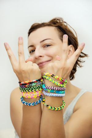 Smiling young woman with colorful rubber bracelets on her hands. Beauty and fashion. photo