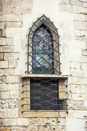 Barred window on church wall. Architectural elements. photo