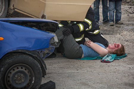 salvaging: Nitra, Slovakia - September 06, 2014: Simulation of the car accident. Firefighters saving the bleeding woman from a crashed car.