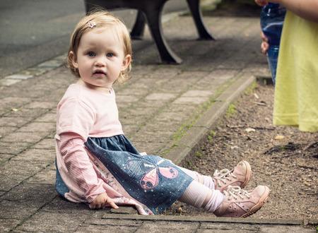 sitting on the ground: Little caucasian blond girl in beautiful dress sitting on the ground. Stock Photo