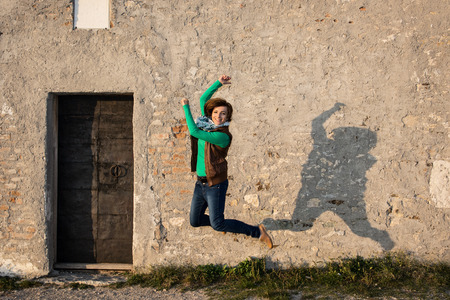 Young caucasian woman is jumping for joy in front of the old wall. photo
