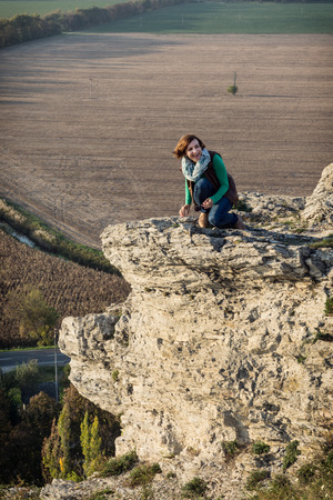 Young woman posing on the high rock at sunset. photo