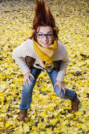 Young woman posing with hair in autumn leaves. Beauty and fashion. photo