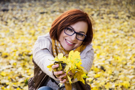 Smiling redhead woman with yellow autumn leaves. Seasonal theme. photo