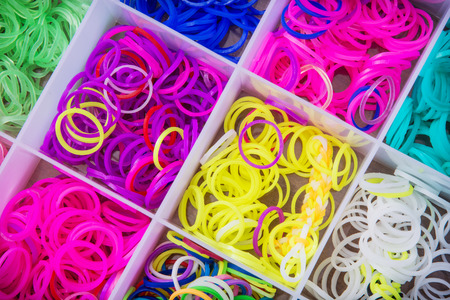 rubber bands: Big box with colorful rubber bands for rainbow loom. Handiwork theme. Leisure activity. Stock Photo