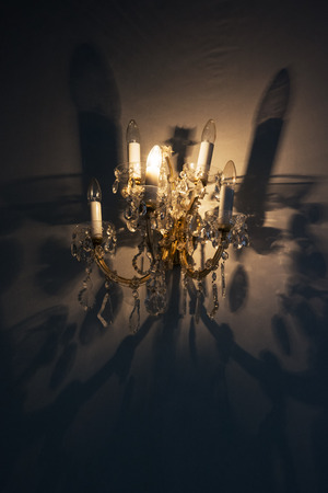 electrolier: Porcelain chandelier on the wall and magic shadow. Old interior theme. Stock Photo