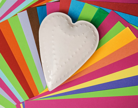White metal heart on a colorful papers. Valentines Day. photo