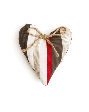 skillfully: Decorative valentine heart of fabric with ribbon on a white background.