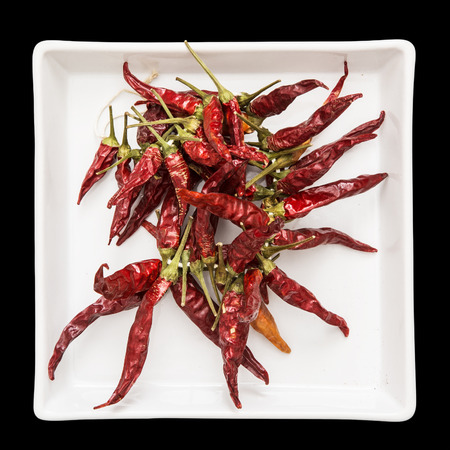 Red dry chillies in the white bowl.