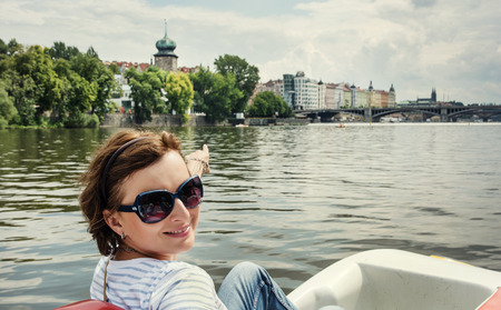 Young woman on the boat, Vltava, Prague. Travel destination.