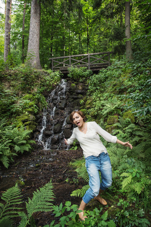 inattention: Young woman falls into water. Wooden bridge and waterfall. Hiking theme. Stock Photo