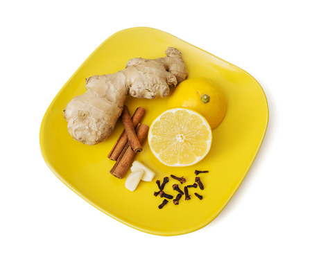 Ginger, cinnamon, lemon, garlic and cloves on the plate. Healthy food. photo