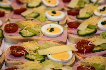 multi grain sandwich: Sandwiches with egg, cheese, cucumber, ham and cherry tomatoes. Food and drink theme.