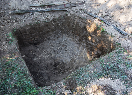 mud pit: Square hole in the ground. Stock Photo